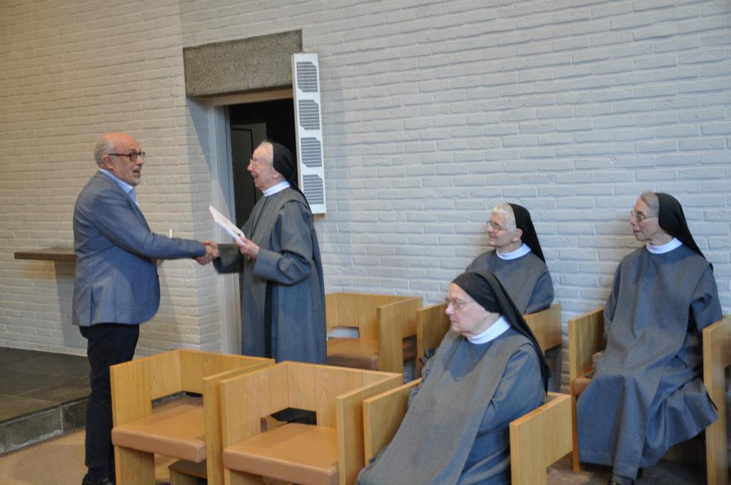 Toon Osaer overhandigt een exemplaar van het boek aan de zusters, als dank voor hun gastvrijheid.